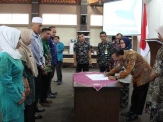 Sekdakab Azwirman menandatangani berkas sosialisasi.