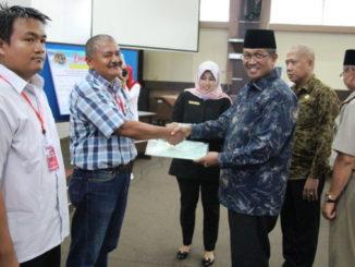 Bupati Gusmal menyerahkan sertifikat aset Pemkab Solok.
