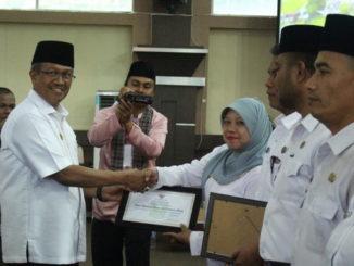 Bupati Gusmal menyerahkan penghargaan kepad pelaksana Musrembang terbaik.