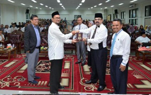 Penyerahan cendra mata dari Rektor IAIN Batusangkar DR.H. Kasmuri kepada tim Asesor BAN-PT Dr.Fakri Husein, SE, M,Si.
