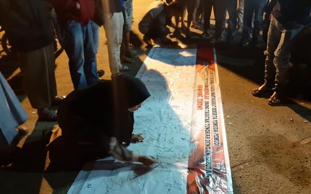 Warga Situjuh menandatangani spanduk penolakan pemberian nama Kampung Jokowi di Dusun Taratak, Situjuh.