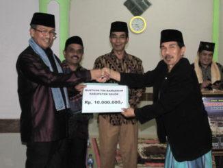 Bupati Gusmal menyerahkan bantuan ke pengurus Mushalla Nurul Falah.
