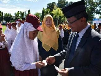 Bupati Indra Catri menyerahkan blanko KIA kepada salah seorang murid SD.