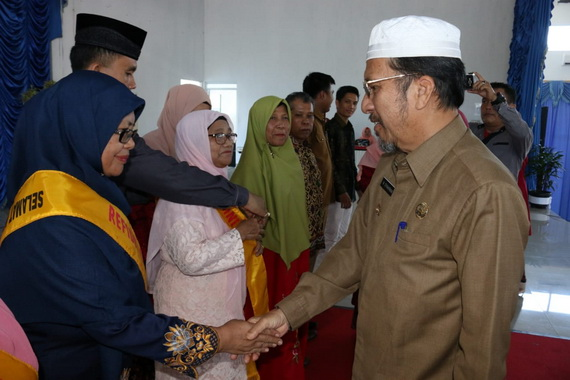 Bupati Syahiran saat menyalami salah seorang guru SMPN 1 Pasaman yang memasuki masa pensiun.