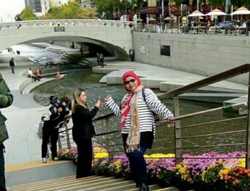Elmar menikmati sore di antara banyak turis lain di tepian Sungai Cheonggyecheon, Kota Seoul