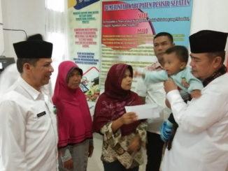 Wagub Nasrul Abit menggendong anak (Alm) Dendi saat pemberian santunan.