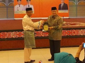 Wagub Sumbar Nasrul Abit menerima plakat dari Gubernur Kalbar.