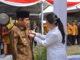 Bupati Sijunjung Yuswir Arifin tengah disematkan tsnda kehormatan Satyalencana oleh Menko PMK, Puan Maharani.