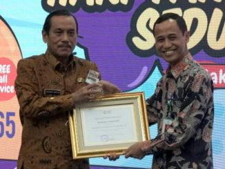 Bupati Sijunjung, Yuswir Arifin tengah menerima piagam penghargaan Pastika Parahita yang diserahkan Dirjen P2P Agung Sugihantono.