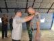 Wakil Bupati Sijunjung, Arrival Boy tengah memasangkan tanda peserta pada pelatihan bela negara