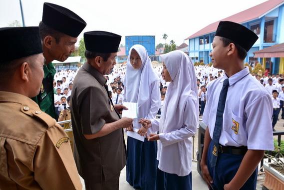Bupati Sijunjung Yuswir Arifin (kiri) tengah menyerahkan bantuan dana pendidikan yang berasal dari Baznas untuk siswa kurang mampu.