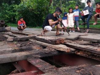 Masyarakat saat mencoba memperbaiki jembatan Sawah Sudut seadanya.