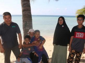 Putra (kiri) bersama keluarga di salah satu pantai Sumba.