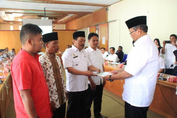 Bupati Gusmal menyerahkan berkas rapat kepada Camat Tigo Lurah.