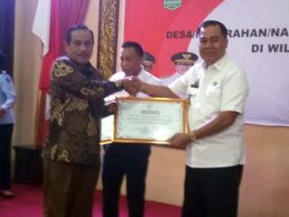 Bupati Sijunjung, Yuswir Arifin tengah menerima penghargaan Anubhawa Sasana Desa dari Kepala Badan Pembinaan Hukum Nasional Republik Indonesia, prof.Dr.H.R.Benny Riyanto, SH, M.Hum, CN.