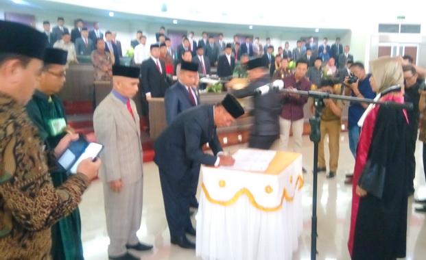 Ketua DPRD Kabupaten Sijunjung Periode 2019 - 2024, Bambang Surya Irawan tengah membubuhi tandatangan pada naskah sumpahjanji.