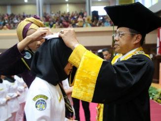 Rektor Ganefri memasangkan cup kepada salah seorang mahasiswa D3 Keperaawatan UNP.