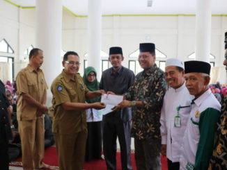 Bupati Irfendi Arbi didampingi ketua BAZNAS Desembri P Caniago dserahkan bantuan sekolah anak kurang mampu secara simbolis.