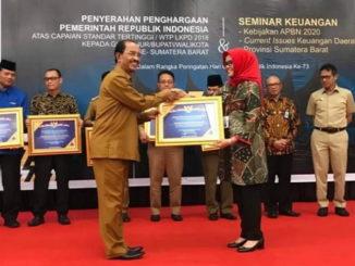 Bupati Pasaman H.Yusuf Lubis saat menerima piagam penghargaan WTP yang diserahkan Sekretaris Dirjen Perbendaharaan Kementrian Keuangan, Regina Maria Wiwieng Handayaningsih, SH.