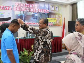 Bupati Gusmal memasangkan tanda peserta pelatihan.