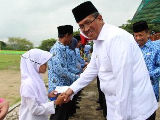 Bupati Gusmal menyerahkan bantuan kepada siswa kurang mampu.