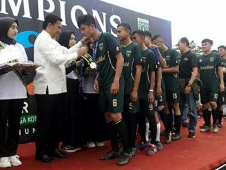 Sekdako Sony mengalungkan medali emas kepada tim Kelurahan Balai Balai