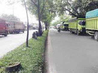 Truk yang parkir sepanjang jalan raya Indarung.