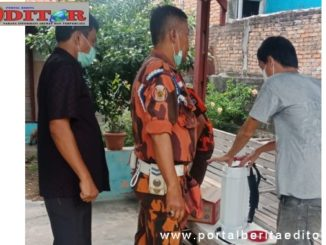 Anggota DPRD Kota Padang, Helmi Moesim bersama MPC PP mencek pengisian cairan disinfektan yang akan disemprotkan.
