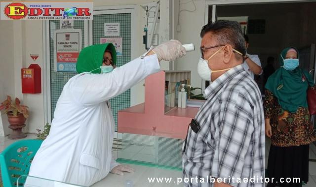 Ketua Komisi IV DPRD Kota Padang, Azwar Siri tengah di periksa oleh pegawai Dinas Kesehatan Kota dengan alat pengukur suhu tubuh.
