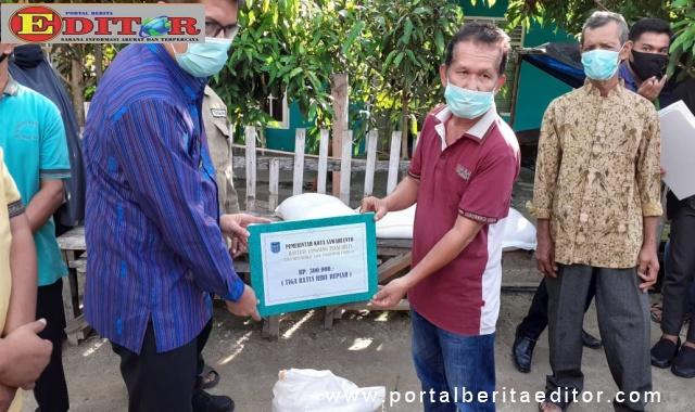 Walikota Sawahlunto saat menyerahkan bantuan terhadap salah seorang warga Kelirahan Pasar.