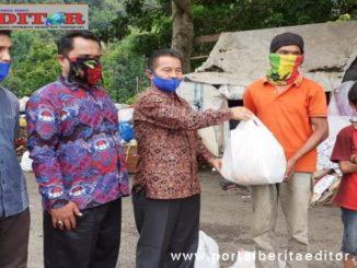 Kadis Sosial PMD Solsel Zulkaranini didampingi Wali Nagari Lubuk Gadang serahkan bantuan kepada pemulung yang tinggal di dekat tumpukan sampah.