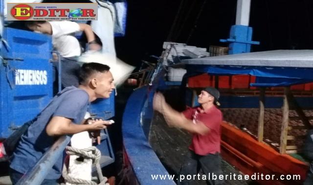 Pemuatan beras bantuan ke kapal antar pulau.