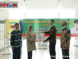 Assisten Administrasi Umum Pemkab Tanah Datar Helfi Rahmi Harum menyerahkan SPPT PBB-P2 kepada perwakilan Camat.