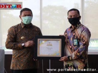 Feri Irawan dan Wako Ramlan Nurmatias dengan penghargaan yang berhasil diraih.