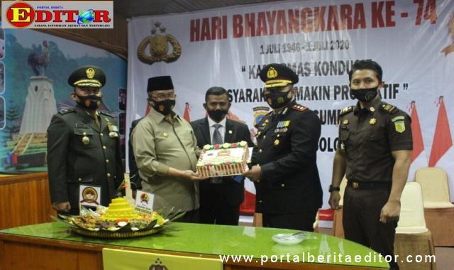 Bupati Gusmal menyerahkan kue HUT Bhayangkara ke 74 kepada Kapolres Solok Arosuka.