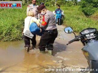 Kapolsek saat membantu warga melewati jalan yang tertutup bajir.