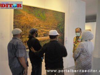 Novermal Yuska anggota DPRD Kab. Pesisir Selatan saat mengamati salah satu lukisan didampingi KadisKebudayaa, Gemala Ranti.