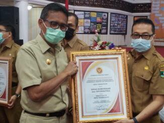 Gubernur Irwan Prayitno menyerahkan penghargaan kepada Kadis Kominfo, Jasman Rizal.