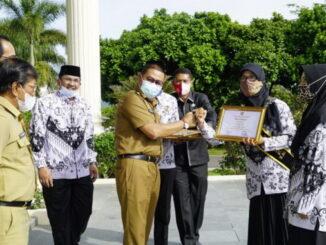 Wako Ramlan serahkan penghargaan kepada guru berprestasi pada upacara peringatan hari Guru.