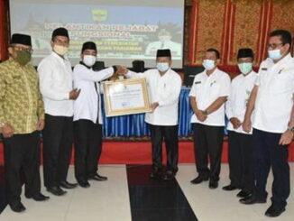 Ketua Baznas Dr Rahmat Tk Sulaiman meperhatkan piagam pengharrgaan yang diserahkan pengurus Baznas Pusat,
