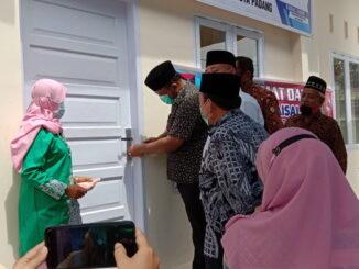 Camat Nanggalo Fuji Astomi saat membuka kunci pintu Balai Pemuda RW 4 Kkelurahan Surau Gadang sebagai tanda peresmian pemakaian gedung baru