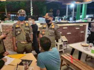 Tim yustisi Payakumhuh menertibkan pengunjung salah satu cafe .