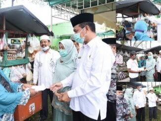 Wako Genius Umar menyerahkan bantuan kepad pedagang sayur keliling.