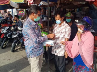 Gubernur Irwan Prayitno saat membagikan masker.