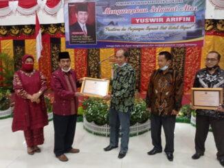 Pimred Portal Berita Editor, Yurnaldi tengah menerima penghargaan dari Bupati Sijunjung, Yuswir Arifin (kiri).