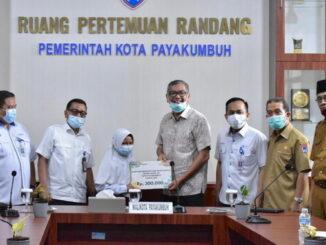 Wako Payakumhuh menyerahkan dana CRS bidang pendidikan dari Bank Nagari kepada perwakilan pelajar SD disaksikan petinggi Bank Nagari Kadis pendidikan Payakumbuh.