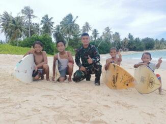Anggota Satgas TMMD ke 110 main surfing bersama anak-anak di pantai Mapadegat.
