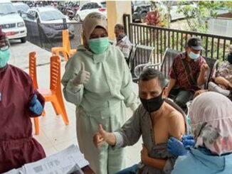 Ketua Jurim Puskesmas Lima Kaum Evi Darmaizal sedang memvaksin salah seorang lansia.
