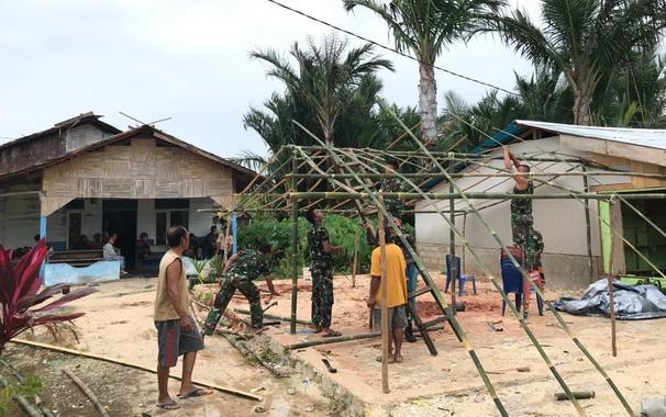 Anggota Satgas TMMD saat ikut memasang tenda di Mapadegat.