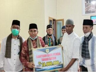 Kepala BKD Adrion Nurdal menyerahkan bantuan Tim II Safari Ramadhan kepada Pengurus Masjid Nurul Yakin Aua Duri Nagari Batu Bulek.